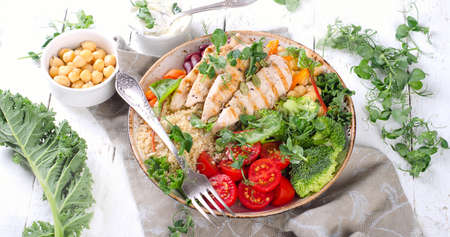 Healthy bowl with grilled chicken, quinoa, chickpea, kale, broccoli and tomato Stock Photo