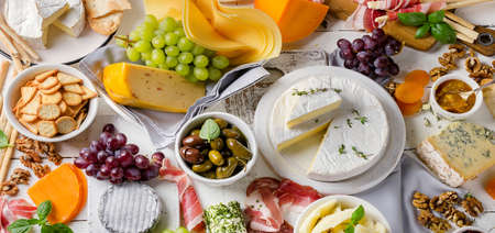 Charcuterie assortment, cheeses, olives and fruits   on a white wooden background. Archivio Fotografico