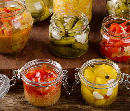 Fermented preserved vegetables on a rustic wooden background.  Imagens