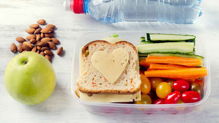 Healthy lunch box with sandwich and fresh vegetables, bottle of water. Healthy eating concept. Top view Standard-Bild
