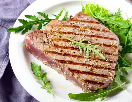 Grilled tuna with fresh green salad leaves. Top view Stock Photo