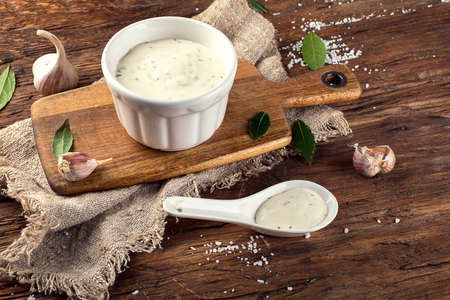 Bowl of Garlic sauce or mayonnaise on a wooden board.