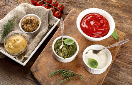 Bowls of various sauces on rustic wooden board. View from above Stock Photo