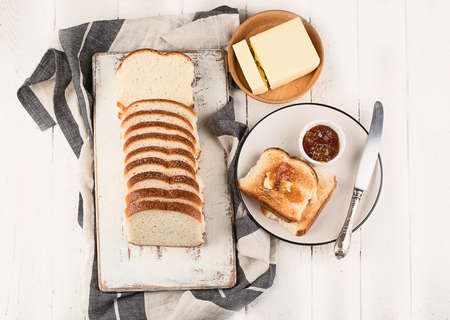 Cutting board with toast bread, jam and butter on table. Top view