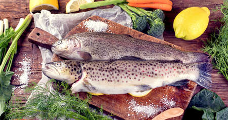 Fresh fish and ingredients for cooking o wooden background. Top view.