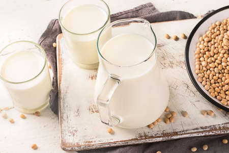Soymilk and soybean on wooden table. Vegan and vegetarian food concept