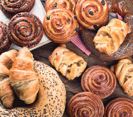 Breads,  buns, croissants. Bakery ingredients on wooden background. Breakfast food concept. Top view