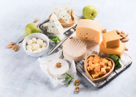 Different kinds of cheeses on rustic wooden board.