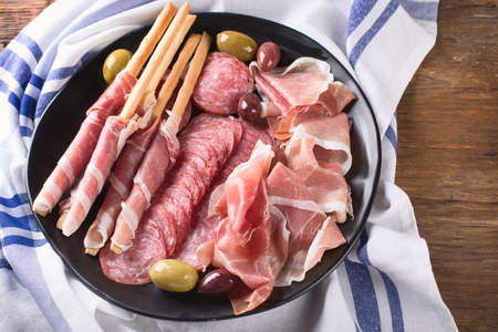 Plate with prosciutto, salami, bread sticks and olives. Top view