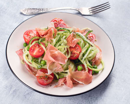 Cucumber and tomato salad with prosciutto. Healthy diet eating