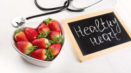 Fresh strawberry in heart shape bowl. Healthy food concept. top view Stock Photo