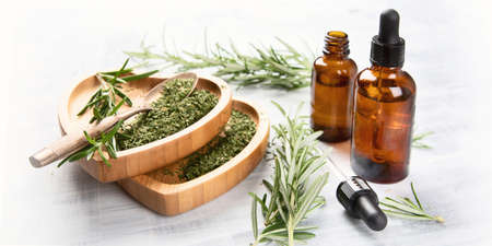 Natural rosemary essential oil with fresh rosemary twigs Stock Photo
