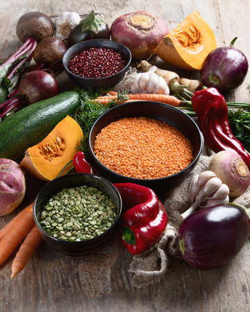 Healthy organic food. Mixed legumes and vegetables on rustic background