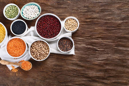 Various dry legumes on wooden board. Top view with copy space Banque d'images