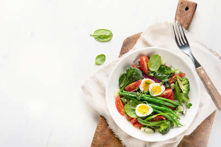 Fresh vegetables  salad with eggs, green beans, broccoli and tomatoes. Diet menu. Healthy eating. Top view with copy space