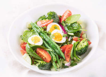 Fresh vegetables  salad with eggs, green beans, broccoli and tomatoes. Diet menu. Healthy eating. Selective focus
