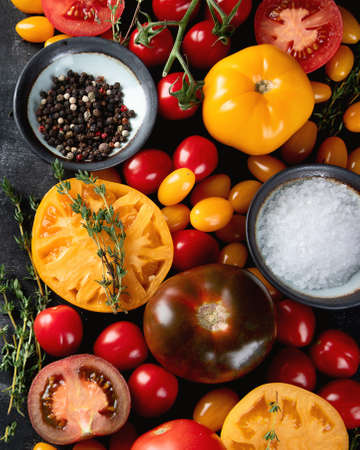 Colorful tomatoes on black background. Top view, flat lay. Healthy food concept Stock Photo