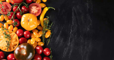 Colorful tomatoes on black background. Top view, flat lay with copy space. Healthy food concept.