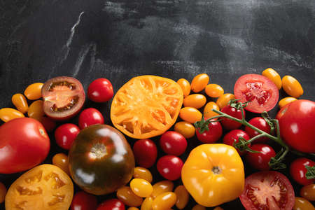 Colorful tomatoes on black background. Top view, flat lay with copy space. Healthy food concept Stock Photo