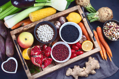 Fresh vegetables and legumes in wooden box. Organic food. Vegan food ingredients. Healthy eating concept. Flat lat, top view Stock Photo