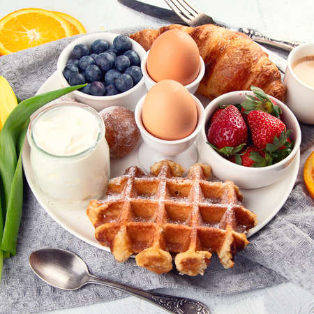 Breakfast table with eggs, berries, yogurt,waffle and croissant. Top view with copy space Stock Photo