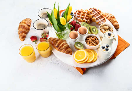 Breakfast table with eggs, berries, yogurt,waffle and croissant. Image with copy space