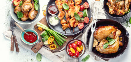 Grilled chicken meat meals on table. Assortment of tasty bbq snack with fresh vegetables. Panorama, banner. Top view