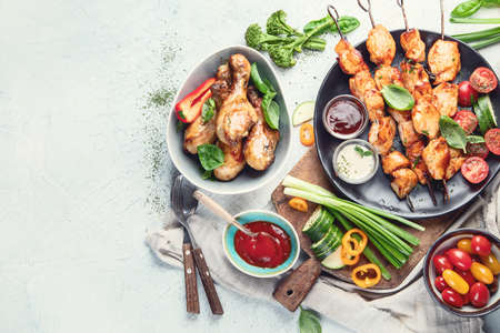 Grilled chicken meat meals on table. Assortment of tasty bbq snack with fresh vegetables. Top view with copy space