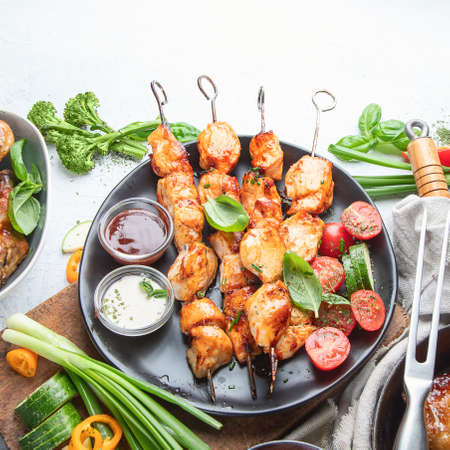 Grilled chicken meat meals on table. Assortment of tasty bbq snack with fresh vegetables Imagens