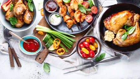 Grilled chicken meat meals on table. Assortment of tasty bbq snack with fresh vegetables. Top view, flat lay