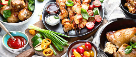 Grilled chicken meat meals on table. Assortment of tasty bbq snack with fresh vegetables. Panorama, banner