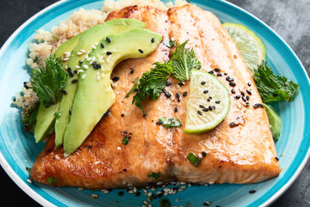 Grilled salmon with avocado, quinoa and sesame on black Stok Fotoğraf