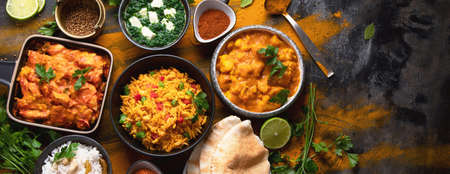 Assorted indian food on black background. Indian cuisine. Top view with copy space. Panorama, banner