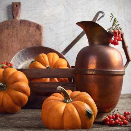 Autumn seasonal cooking concept with pumpkins and kitchen utensils. Front view