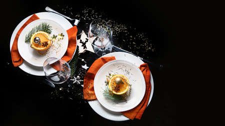 Christmas table setting. Holiday Decorations on black background. Top view, flat lay with copy space