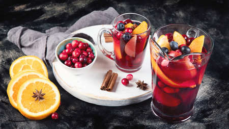 Cranberry and orange winter sangria or mulled wine on dark