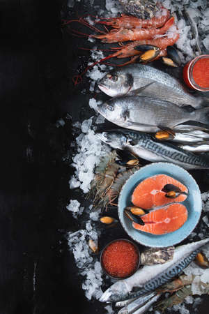 Fresh fish and seafood on black background. Top view with copy space 版權商用圖片