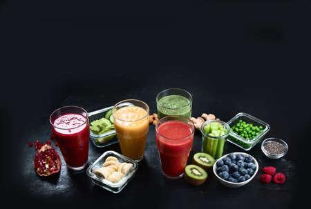 Diferentes tipos de batidos sobre fondo negro. Concepto de dieta sana limpia y desintoxicante. Imagen con espacio de copia Foto de archivo