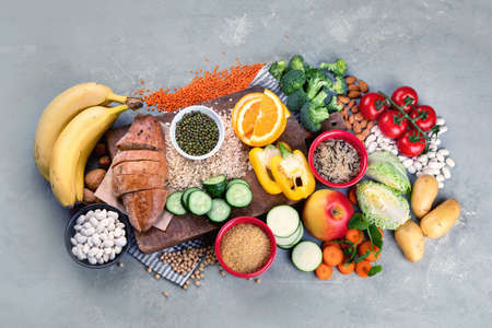 Foods high in carbohydrates on grey background. Vegan Foods high in dietary fiber, antioxidants, vitamins and minerals. Top view, flat lay Archivio Fotografico
