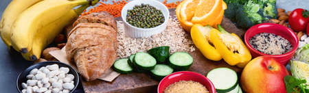 Foods high in carbohydrates on grey background. Vegan Foods high in dietary fiber, antioxidants, vitamins and minerals. Panorama, banner
