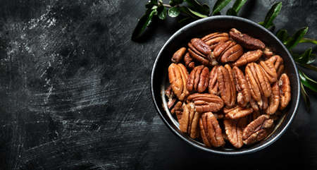 Pecan nuts in bowl. Top view with copy space