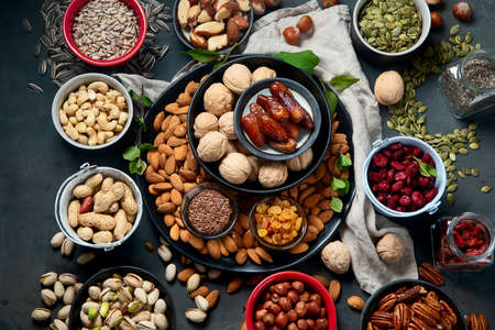 Different types of nuts, seeds and dried fruits on black background. foods high in vegan protein, vitamins and antioxidants for immune system boosting. Top view