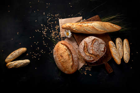 Fresh bread and buns on black background with copy space. View from above.