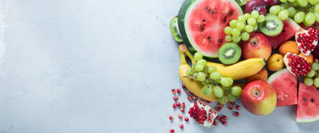 Fresh healthy fruits on grey background. Foods high in antioxidants, carbs, minerals and vitamins. Food for immune boosting. Top view with copy space. Panorama, banner