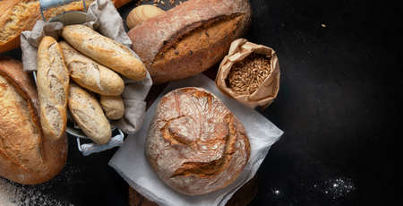 Fresh bread and buns on black background with copy space. View from above. Stock Photo