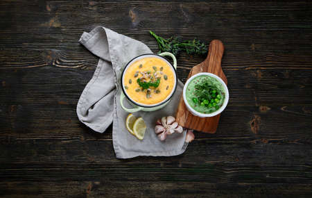 Vegetables cream soups on dark wooden background. Top view with copy space