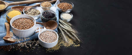 Different types of cereals in bowls on black background. Healthy nutrition eating. Copy space. Panorama, banner.