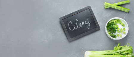 Fresh green organic celery. Celery chopped and celery stalks. Top view, chalkboard, sopy space. Panorama, banner