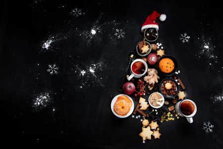 Christmas Tree made of holiday food on black background. Top view, flat lay with copy space. Christmas concept. New Year Holidays background.