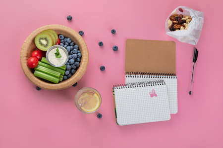 Healthy vegetarian lunch. Berries, fruits and vegetables. Healthy concept with nutrition food. Office desk table with spiral notebook. Top view, flat lay, copy space 版權商用圖片